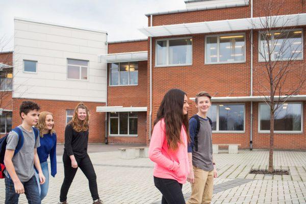 children-12-13-in-front-of-school-building-6PRCE4K