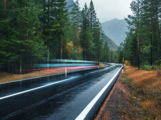 blurred-car-on-the-road-in-spring-forest-in-rain-6A3RPKN