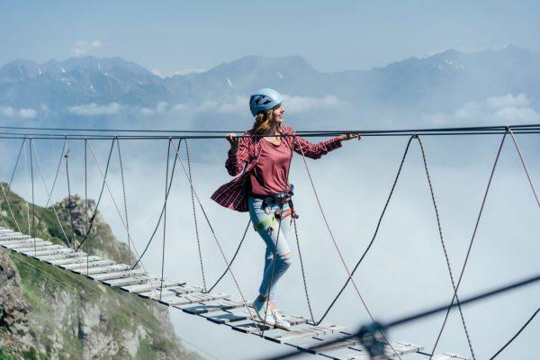 a-happy-cheerful-woman-walks-on-a-suspension-bridg-4FYC3CK