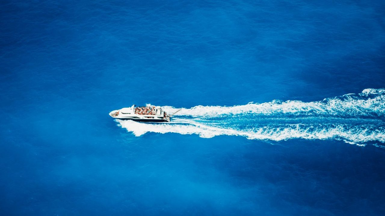 top-view-of-tourist-boat-sailing-in-the-sea-on-ful-LXA58W2