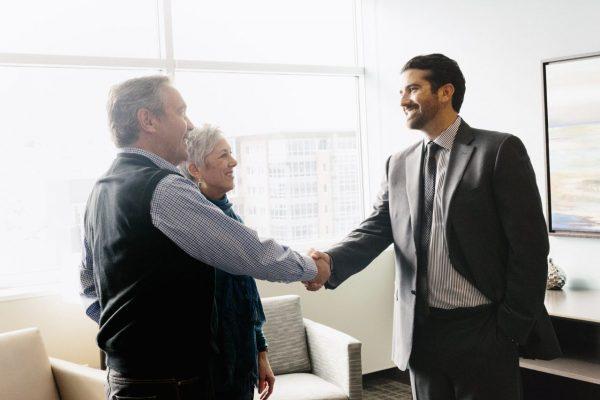 a-man-greeting-a-mature-couple-in-an-office-JG9MKVW